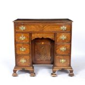 A GEORGE III AND LATER MAHOGANY KNEEHOLE DESK with brushing slide over one long drawer, six short