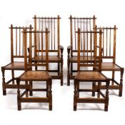 A SET OF SIX ARTS AND CRAFTS STYLE OAK DINING CHAIRS with spindle backs and turned supports to