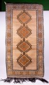 A MIDDLE EASTERN STYLE BROWN HANDMADE WOOLLEN RUG with banded border and four central diamond