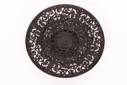 A CAST IRON PLATE with pierced decoration, decorated with hippocampi, tridents and scrolling