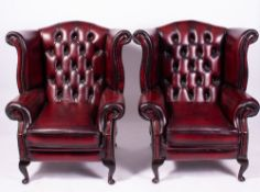 A PAIR OF RED LEATHER UPHOLSTERED WING BACK ARMCHAIRS each 84cm wide x 71cm deep x 102cm high