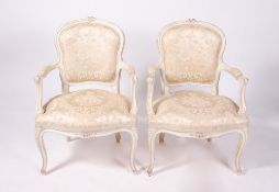 A PAIR OF FRENCH CREAM PAINTED OPEN ARMCHAIRS with upholstered backs and seats, cabriole legs,