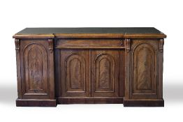 A VICTORIAN MAHOGANY INVERSE BREAKFRONT SIDEBOARD with central drawer and four doors with arching