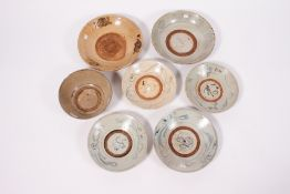 A GROUP OF SEVEN SOUTH EAST ASIAN POTTERY PIECES to include four dishes approximately 25cm diameter,