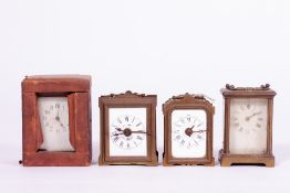 A GROUP OF FOUR MECHANICAL CARRIAGE TYPE CLOCKS two with alarms, one with a case together with two