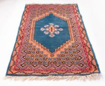 A PERSIAN STYLE TURQUOISE AND ORANGE GROUND WOOLLEN RUG with geometric decoration, 104cm x 194cm