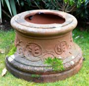 A CAST TERRACOTTA URN STAND of spreading circular form, decorated with masks, 50cm diameter x 33cm