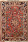 AN EARLY 20TH CENTURY PERSIAN BLUE AND RED GROUND RUG with stylised foliate and peacock