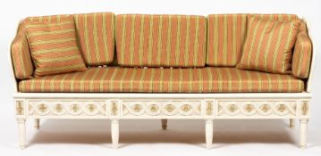 A WHITE PAINTED SOFA with shaped inset back and sides and flowerhead ornament to the carved frieze