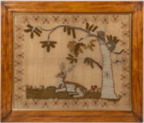 A WILLIAM IV WOOLWORK PICTURE depicting a reclining stag beneath a tree, within a floral border,