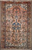 TWO MID TO LATE 20TH CENTURY PERSIAN STYLE RED GROUND WOOLLEN RUGS each with stylised decoration and