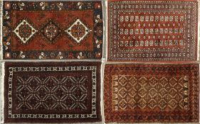 A MIDDLE EASTERN RED AND BLACK GROUND RUG with geometric decoration, 120cm x 198cm together with
