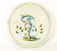 AN 18TH CENTURY CONTINENTAL TIN GLAZED TAZZA centrally decorated with a figure holding a banner,