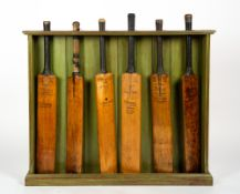 A GREEN PAINTED WOODEN CRICKET BAT STAND complete with six vintage cricket bats, the green painted