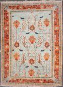 A PAKISTANI ORANGE AND BLUE GROUND RUG with a banded border, stylized foliate decoration, 274cm x