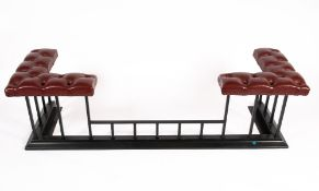 A CONTEMPORARY RED LEATHER BUTTON UPHOLSTERED CLUB FENDER on a black painted wrought iron base,