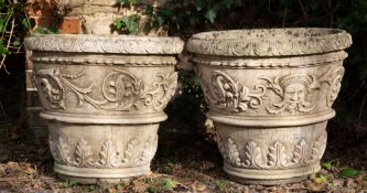 A PAIR OF COMPOSITE STONE URNS decorated with acanthus leaves and face masks, each 54cm diameter x