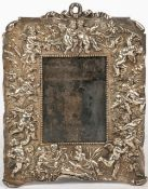 AN OLD SILVER PLATED PHOTOGRAPH FRAME decorated with putti and garlands of flowers around the