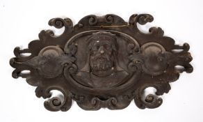 AN ANTIQUE CARVED AND PAINTED PINE CARTOUCHE depicting a bearded monarch, 95cm wide x 55cm high
