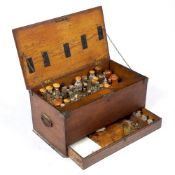 A 19TH CENTURY OAK CASED APOTHECARY OR MEDICINE CHEST containing a number of glass bottles,