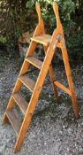 AN OLD STEP LADDER with fluted treads and iron hinge, 93cm front to back x 136cm high when open