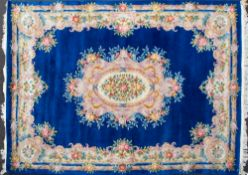 A MID TO LATE 20TH CENTURY CHINESE BLUE GROUND WOOLEN CARPET with stylised floral decoration,