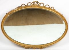 AN OVAL GILT WALL MIRROR with ribbon cresting, 89cm wide x 96cm high overall together with a cream