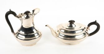 A MATCHING SHEFFIELD SILVER TEAPOT AND HOT WATER JUG each with carved ebony handles and marks for