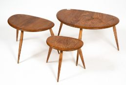 AN ERCOL LIGHT ELM NEST OF THREE OCCASIONAL TABLES with turned legs, the largest 64cm wide x 43cm
