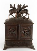 A 19TH CENTURY GERMAN BLACK FOREST TABLE TOP CABINET with carved deer above twin doors with carved