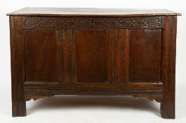 AN ANTIQUE OAK COFFER the twin plank top with cleated ends, the triple panel front with chip