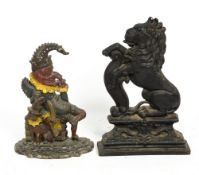 AN OLD PAINTED CAST IRON DOOR STOP OR PORTER in the form of a seated Mr Punch, 23cm wide x 31cm high
