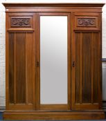 AN EARLY 20TH CENTURY WALNUT MAPLE & CO TRIPLE WARDROBE with central mirrored door and with