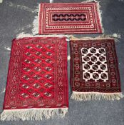 THREE MID TO LATE 20TH CENTURY MIDDLE EASTERN RED GROUND RUGS the largest 103cm x 150cm Condition: