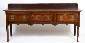 A GEORGE III OAK DRESSER the three drawers with mahogany crossbanded decoration with a shaped frieze
