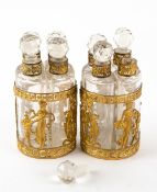 A PAIR OF 19TH CENTURY CONTINENTAL EMPIRE STYLE GILT ORMOLU MOUNTED SETS OF FOUR SCENT BOTTLES
