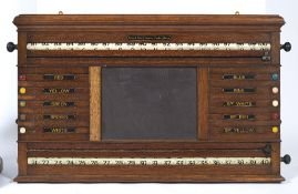 AN OAK WALL HANGING SNOOKER CUE BOARD by Orme & Sons Manchester, London and Glasgow, with central