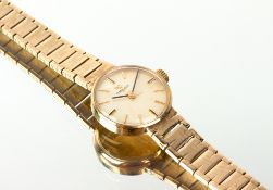 A MID 20TH CENTURY LADIES OMEGA 9 CARAT GOLD COCKTAIL WATCH with a 9 carat gold bracelet strap,