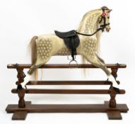 AN EARLY TO MID 20TH CENTURY PAINTED WOODEN ROCKING HORSE on a stained pine frame, overall 140cm