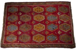 Kelim carpet of red ground with typical red and green stylised panels, 216cm x 343cm