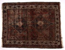 Persian red ground rug with joined central double medallion and with foliate border, 146cm x 112cm