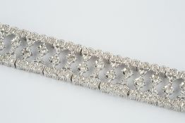 Diamond set panel bracelet designed as a line of articulated openwork panels with central star
