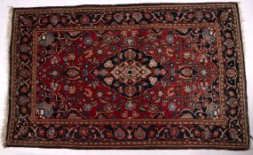 Persian red ground rug with central blue medallion and foliate border, 204cm x 125cm