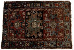 Caucasian polychrome rug with three stylised geometric panels and blue border, 156cm x 107cm