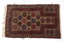 Pakistan rust ground rug with stylised medallions, 146cm x 89cm Condition: fraying to the edge and
