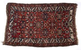 Caucasian red ground rug with foliate medallions and foliate and geometric multiple border, 124cm