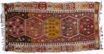 Kelim rug of red ground with five central medallions and with panelled border, 130cm x 240cm