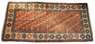 A PERSIAN RUNNER woven with diagonal rows of botehs on a rust coloured ground within a border filled
