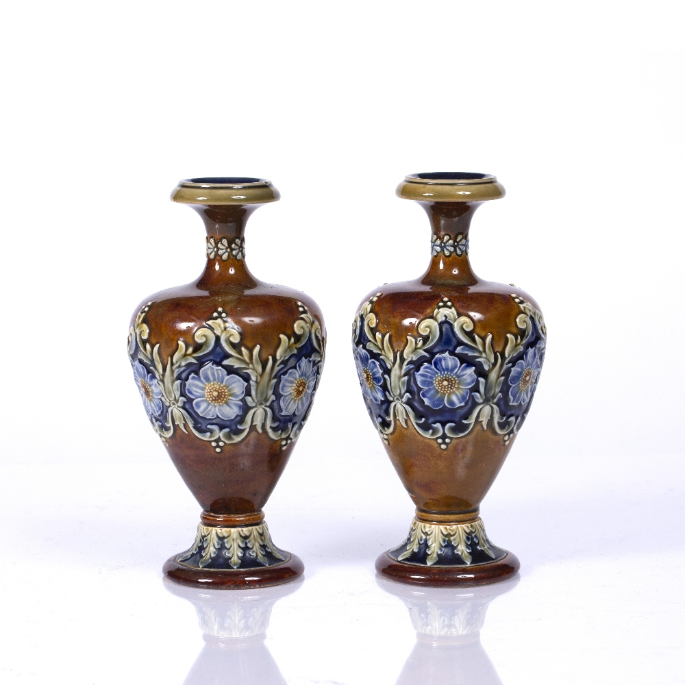A PAIR OF DOULTON LAMBETH BALUSTER VASES each decorated with a band of flower heads and scrolls,