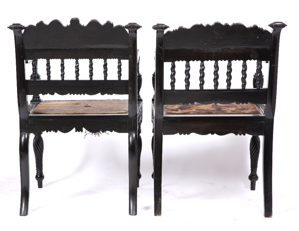 A NEAR PAIR OF EARLY 19TH CENTURY CEYLONESE CARVED EBONY OPEN ARMCHAIRS the foliate crest rails over - Image 4 of 8